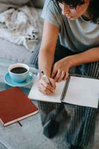 concentrated young lady writing in notepad while studying at home