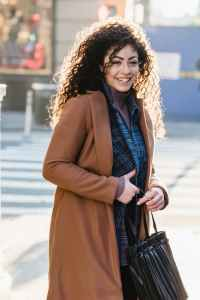 cheerful woman with bag in trendy brown coat smiling