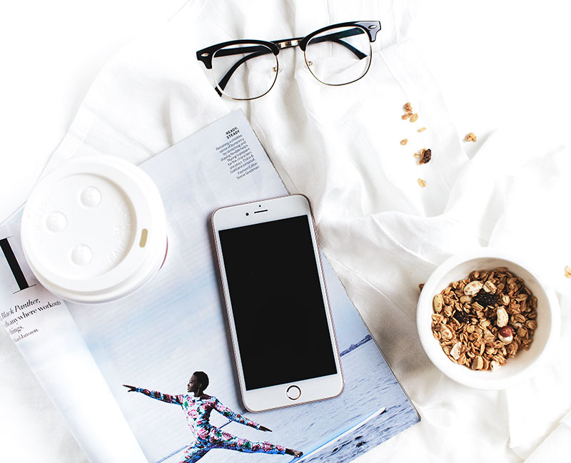 cellphone with glasses and a magazine