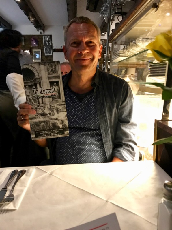 Holding up the menu for the photo to send to me