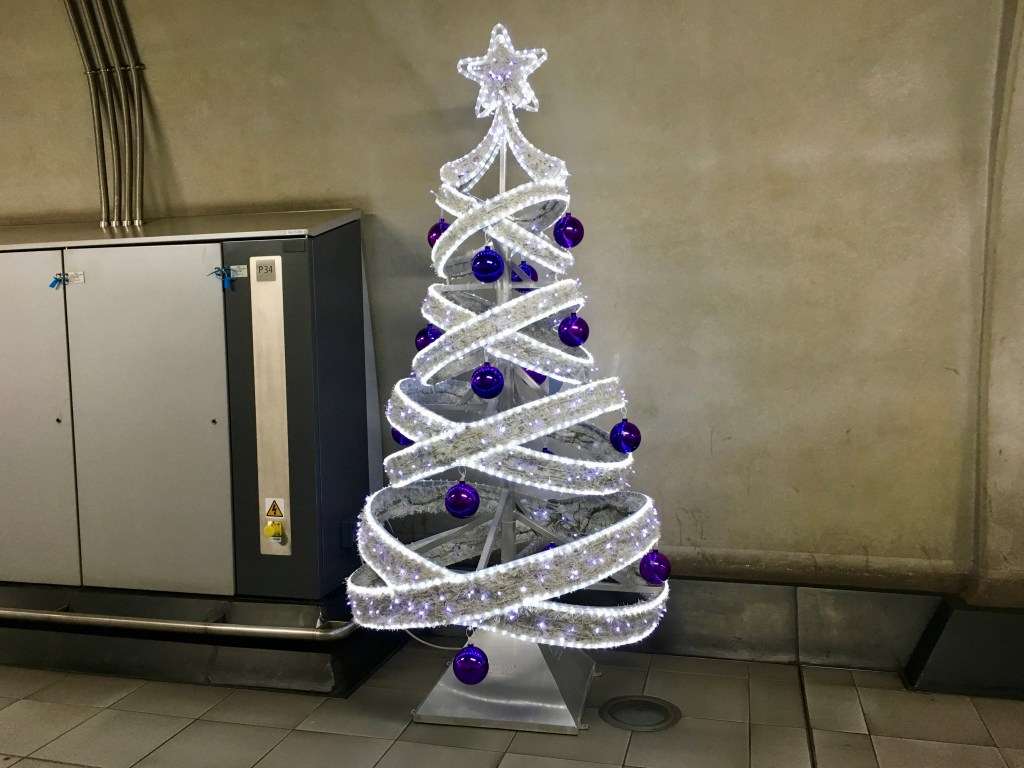 A Charlie Brown tree in a hallway at Heathrow is full of holiday spirit and pluck.
