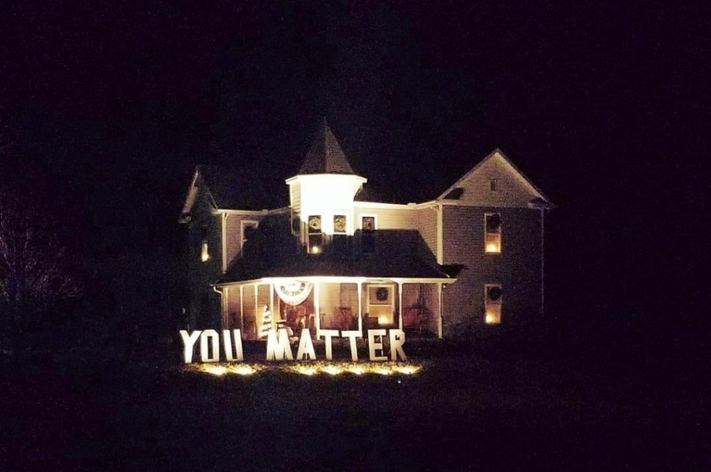 You Matter sign in front of a house, lit up at night