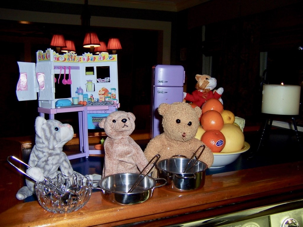 Stuffed animals and a toy kitchen, cooking.