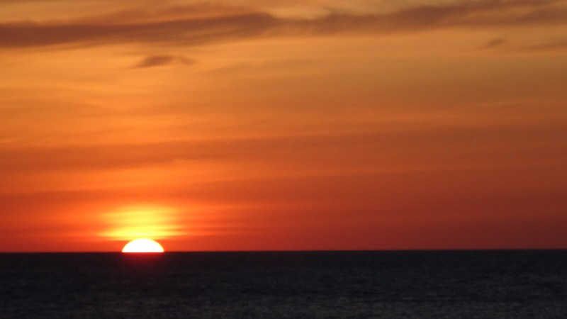 Golden sun disappearing to sea off Gower Peninsula, Wales