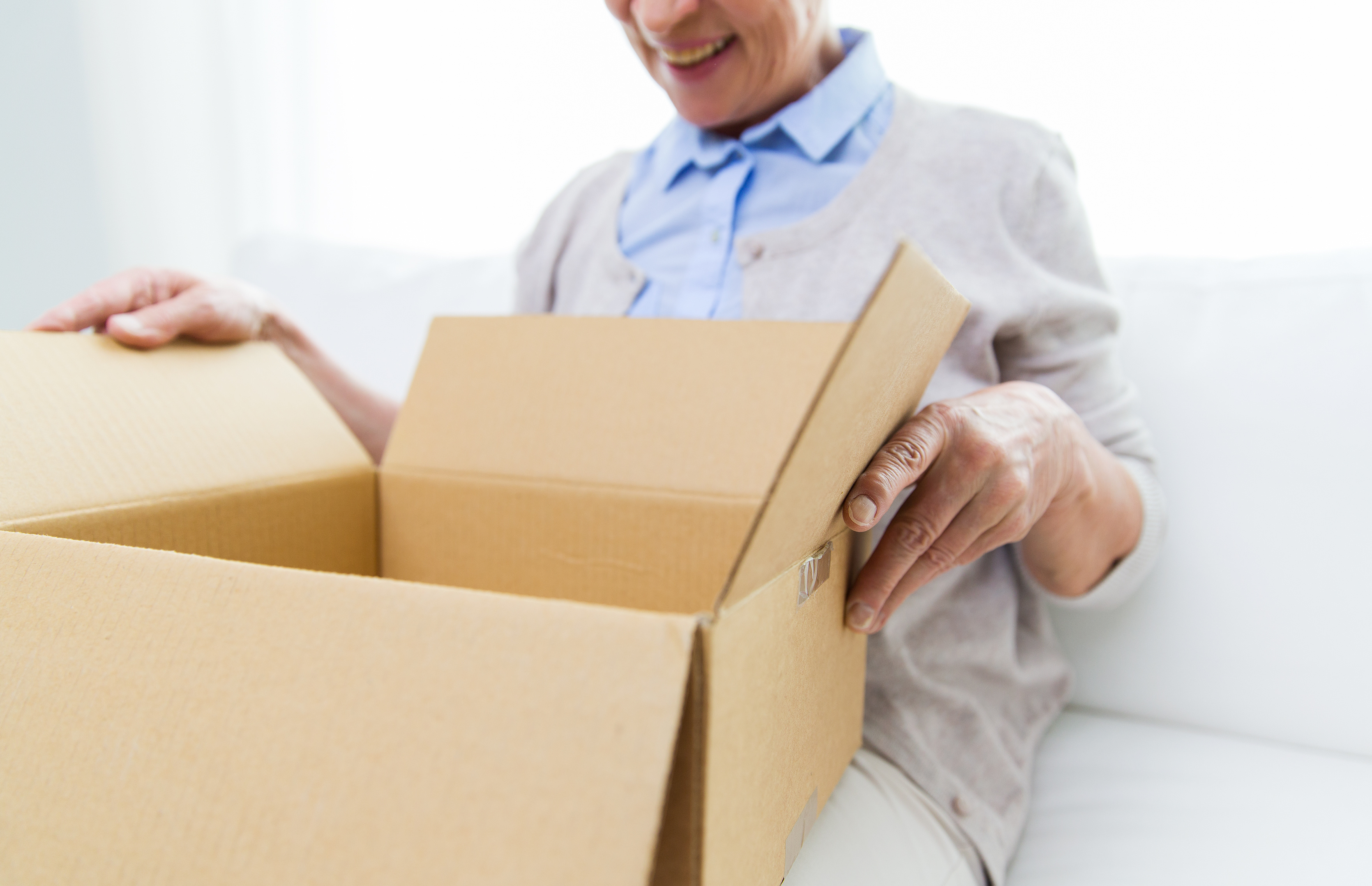 close up of senior woman with parcel box at home