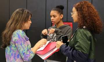English language development teacher Aline Lima, left, directs GLTS juniors Ana Cueto and Melissa Rodriguez, both of Lawrence, to one of the activities held during the pen pal event. (Courtesy Photo GLTS)