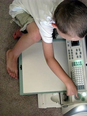 child pushing start button on paper cutting machine