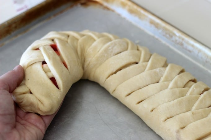 This delicious cherry filled candy cane braided bread is drizzled with a sweet vanilla icing! It's the perfect treat for the holidays.