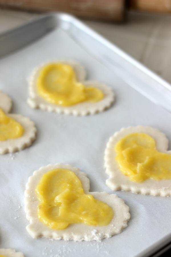 lemon curd spread on pie crust cut out