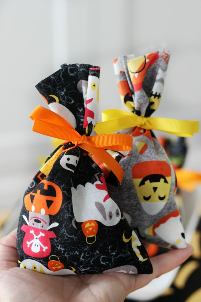 These treat bags are easy to make and fun to fill with candy. Use them as mini BOO kits and doorbell ditch on Halloween! A 2-minute sewing tutorial!