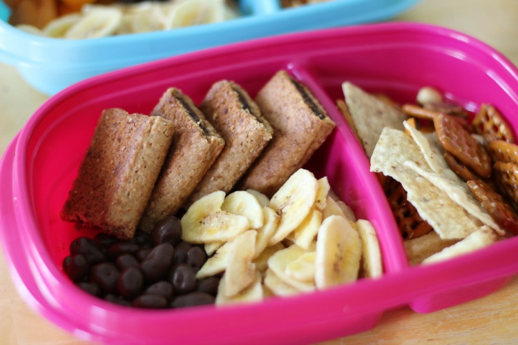 sweet road trip snacks in container fig bars, chocolate raisins and banana chips