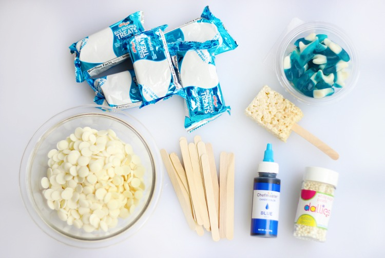 white chocolate in bowl, popsicle sticks, rice krispies treats, gummy sharks, coloring and sprinkles