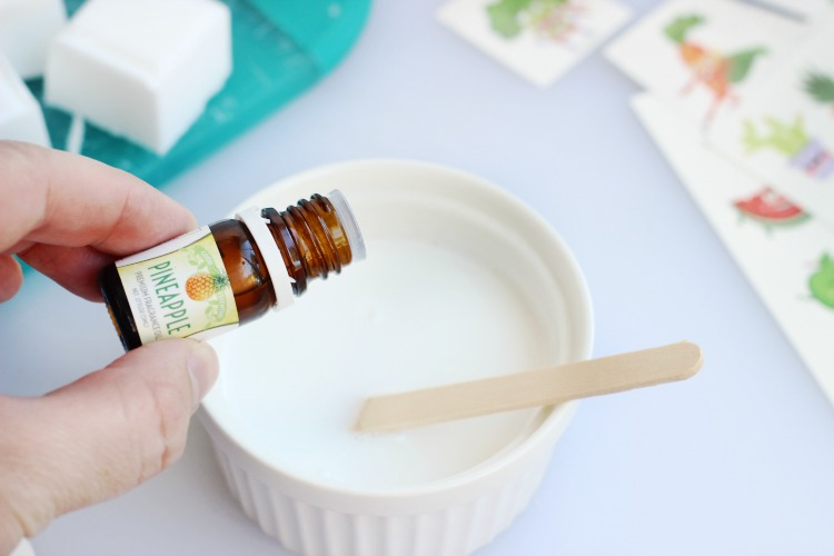 hand adding scent oils to melted soap