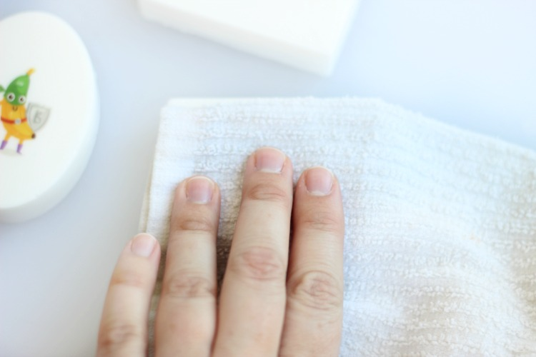 hand placing wet wash cloth over temporary tattoo soap bar