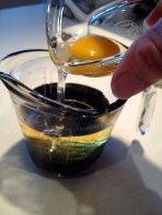 Measuring the walnut oil, molasses, and adding the egg..
