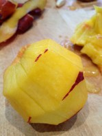 Slicing the peach to the center before carving the fruit off the pit