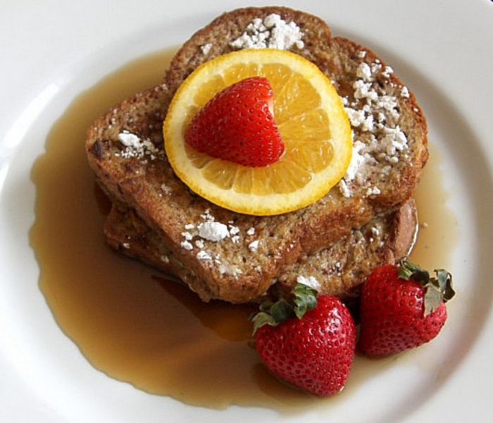 french toast topped with orange slice, strawberries, powdered sugar and syrup