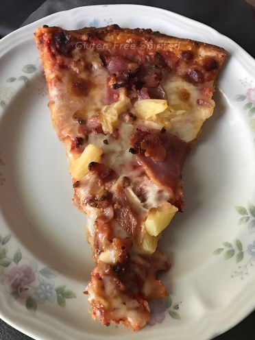 A slice of Domino's pizza with gluten-free crust.