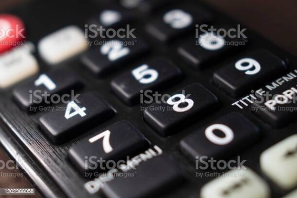 Close up of black remote with white numbers on buttons