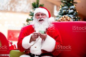 Santa holding a small coffee cup