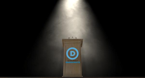 Spotlit podium with Glynn County Demorats logo
