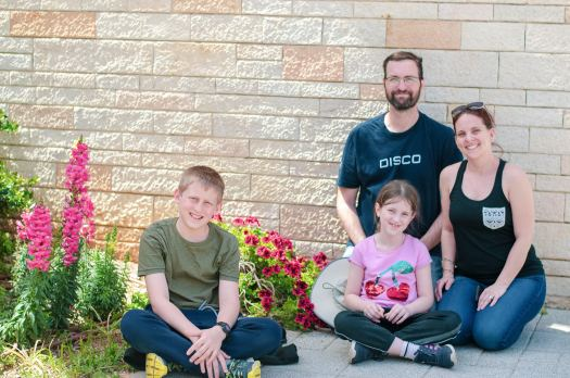 Image of dad, mom and kids sitting on the ground in front of a wall of Jerusalem stone and a bed of colourful flowers.