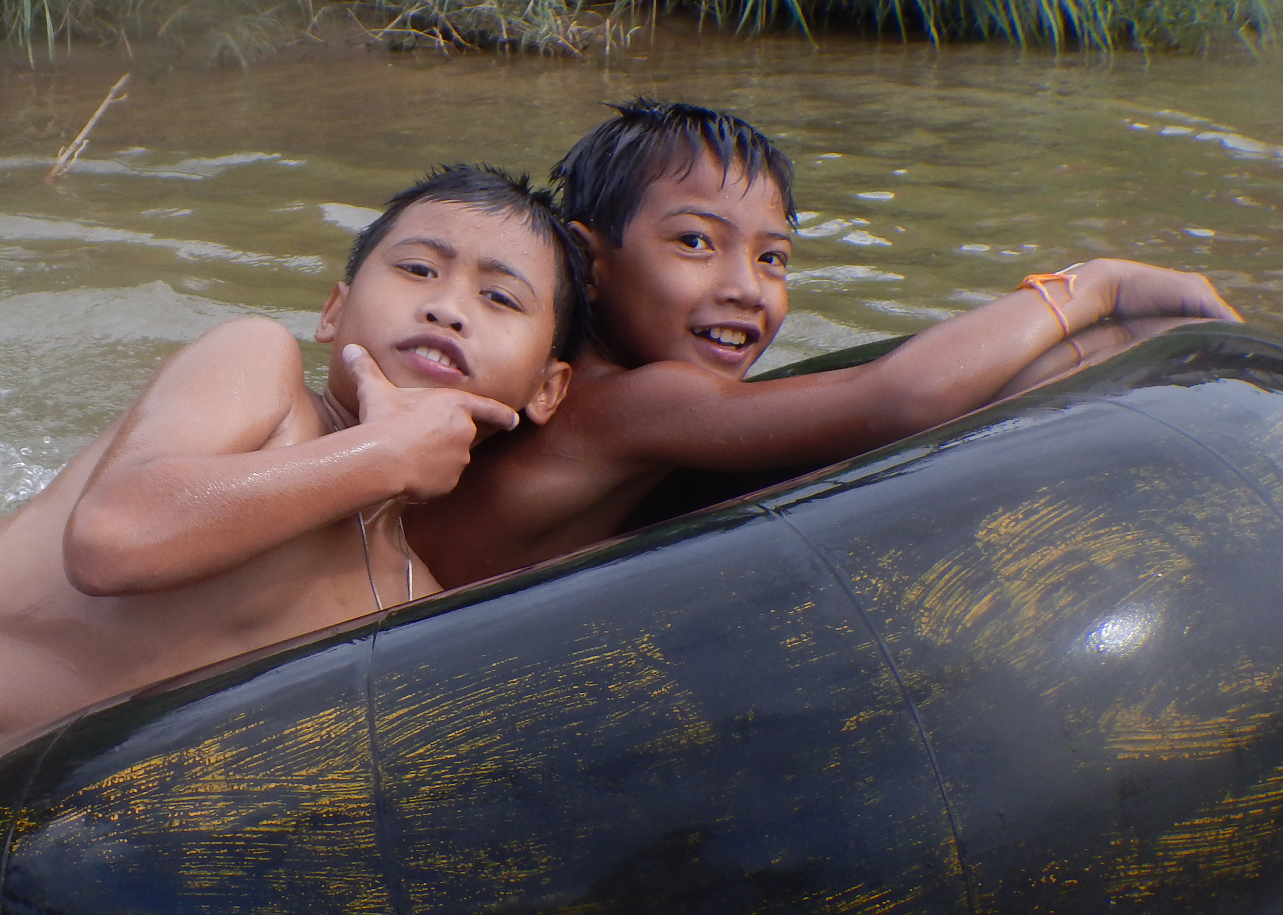 Local boys, floating the Nam Song River in Vang Vieng, Laos