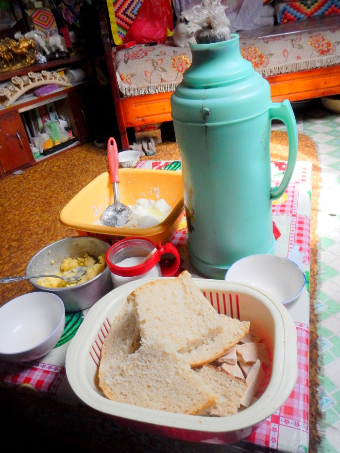 A typical meal in northern Mongolia-- hearty bread, yak cheese, yak butter, sugar (for the bread), and well-salted tea
