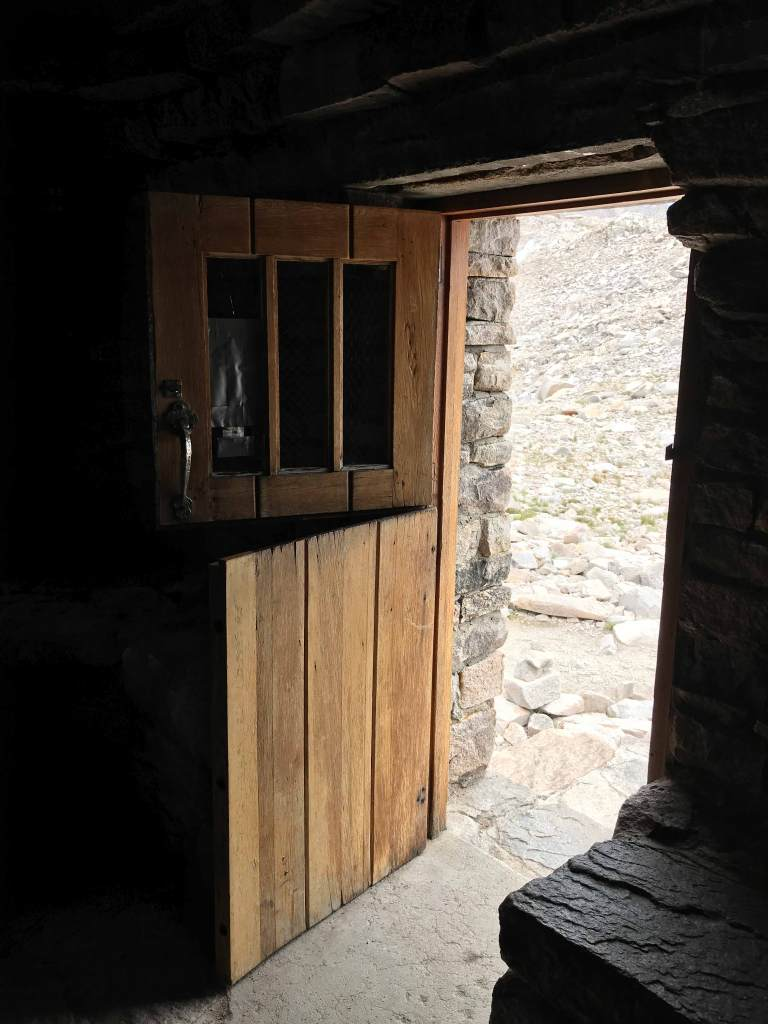 A thick wooden door welcomes visitors to the Muir Hut.