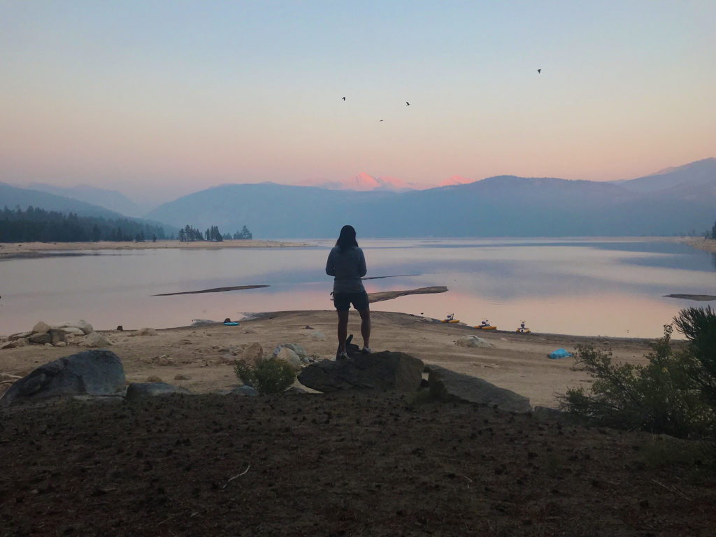 I stand by the shore of Lake Edison at Vermilion Valley Resort watching the alpenglow on the mountains in the distance as the sun sets at the end of the day.