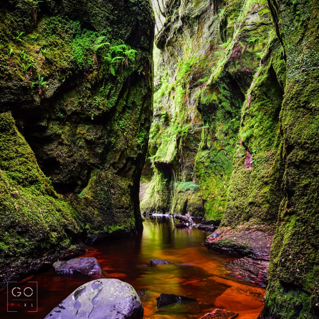 A lovely canyon in Scotland where the green of the moss contrasts with the blood red water