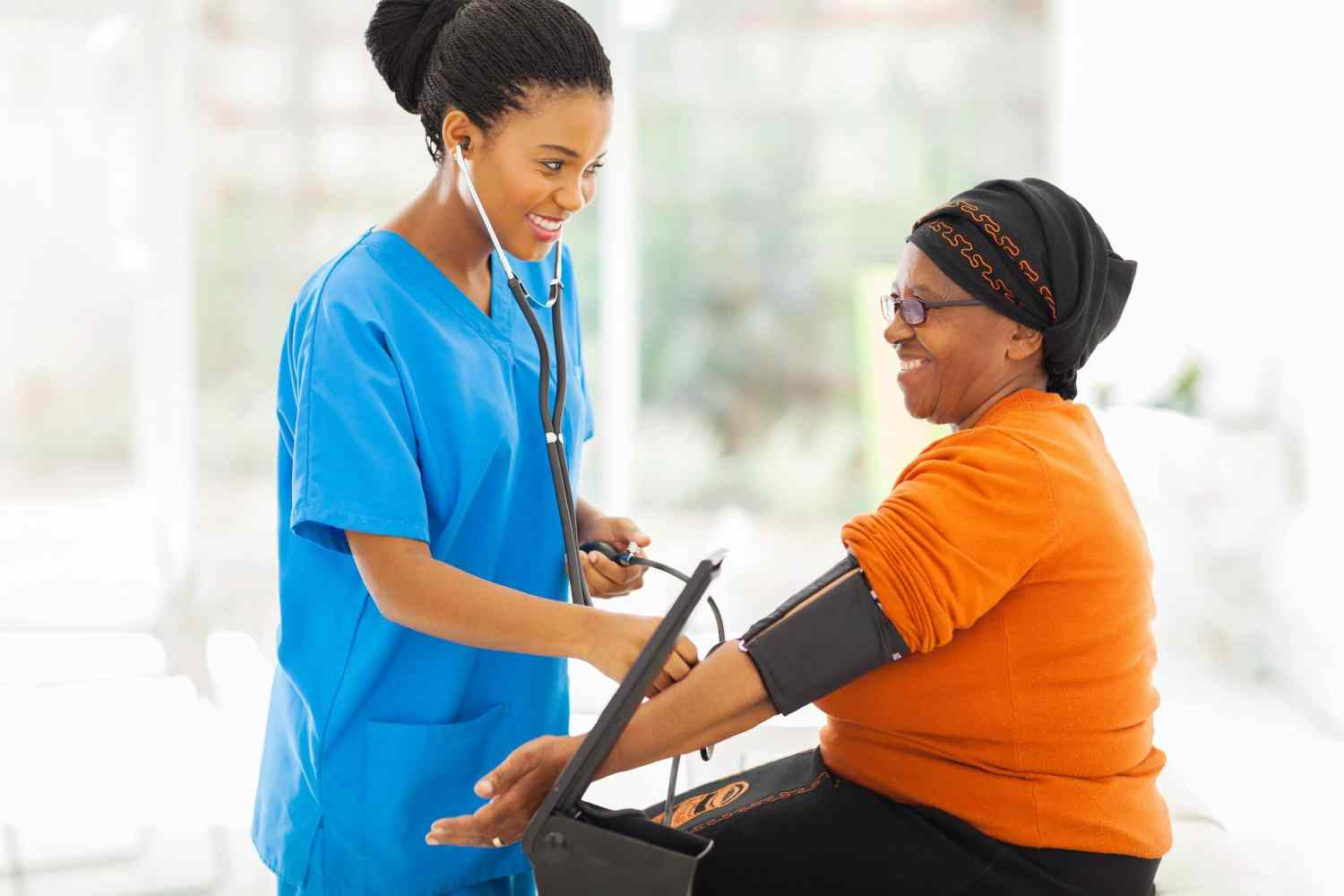 22198042 – smiling african nurse checking senior patient's blood pressure