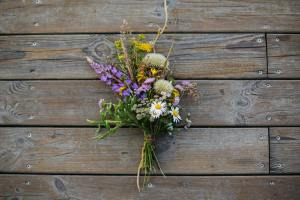 Beautiful bouquet of wildflowers on rustic wood background. Summer vacation in countryside. Top view