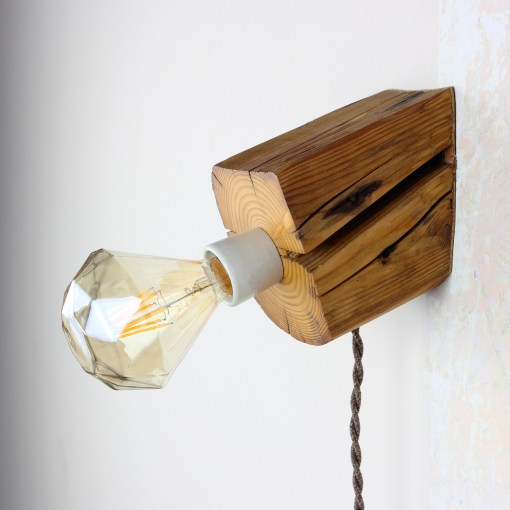 Sloped table and wall lamp from salvaged old barn beam