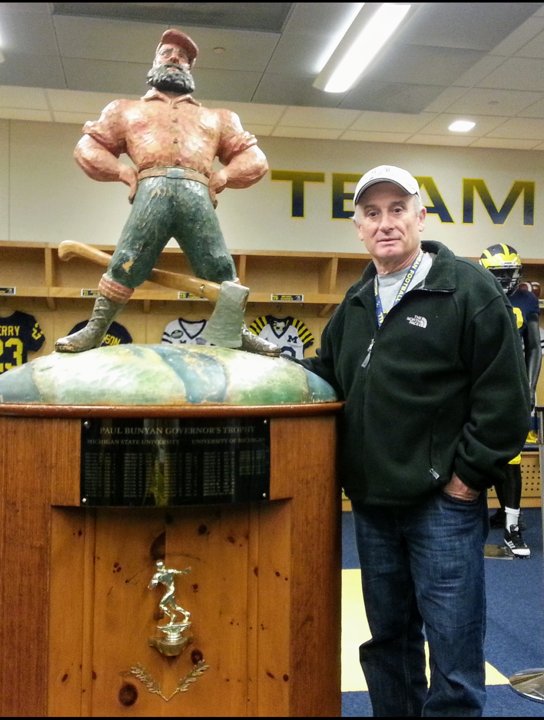 Kevin Kyes (MaizeMan) in the locker room at Michigan with Paul Bunyan trophy