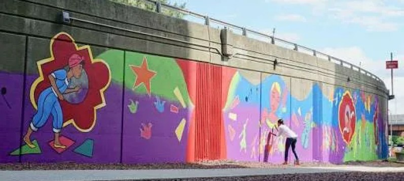 Urban wall that runs along a highway with a vibrant mural painted on it to show an example of art in the Capital Region.