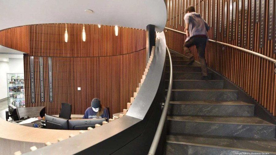 A person sits at a front desk while another person runs up a set of stairs