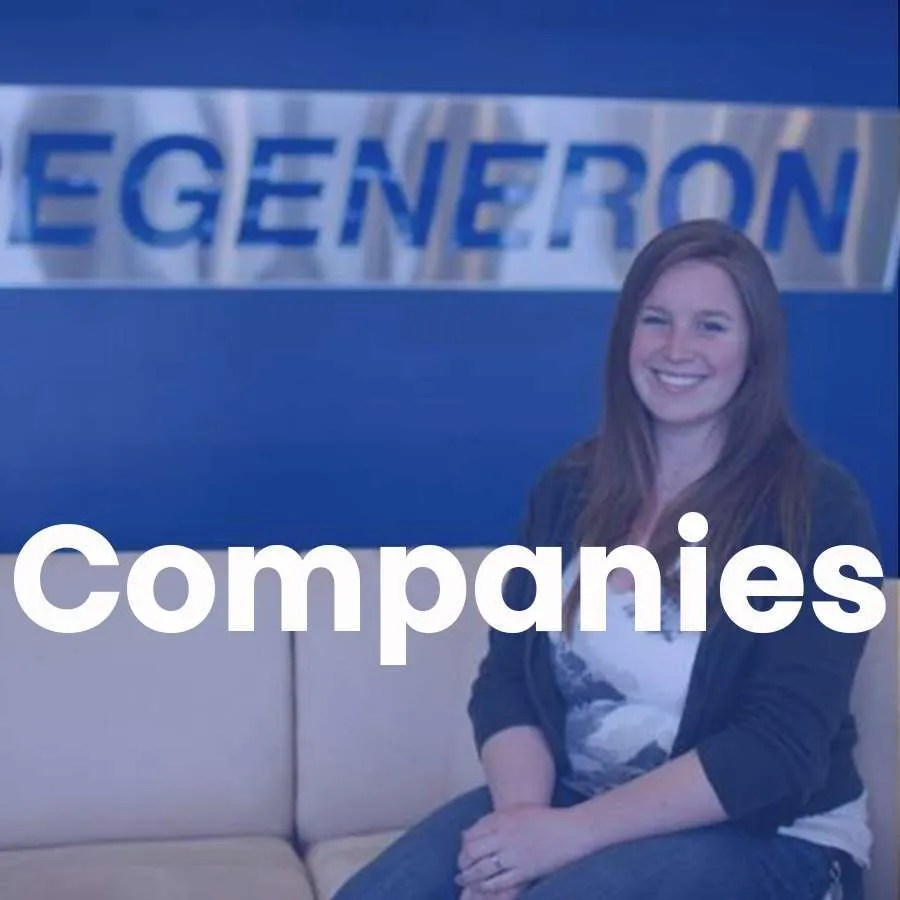 """A woman sits on a couch in front of a Regeneron sign with a super that says """"Companies"""" across."""