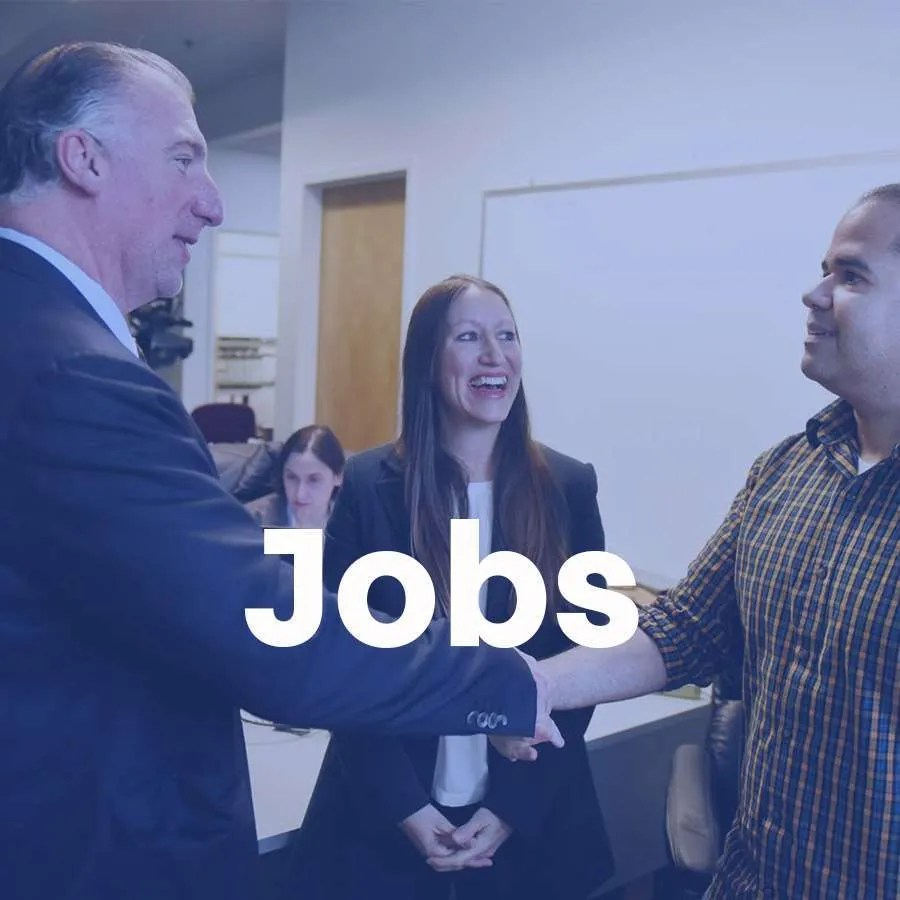"""Two men shake hands while a woman smiles and looks on as a super that says """"Jobs"""" reads across the photo."""