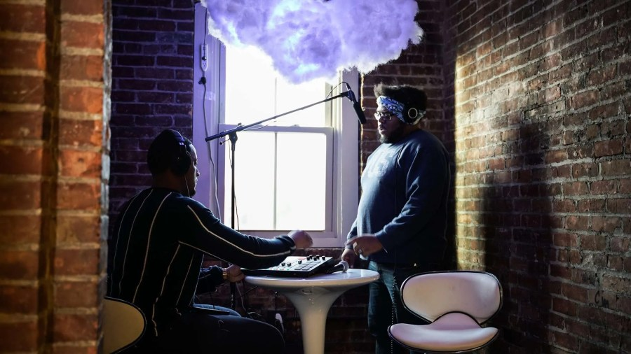 Two young men attend a recording session in a brick room