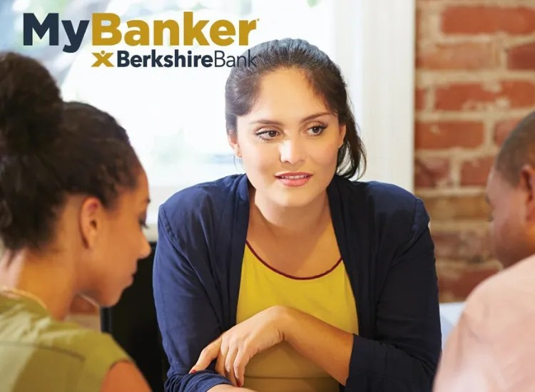 """A businesswoman sits with colleagues. The title on the photo says """"My Banker, Berkshire Bank""""."""