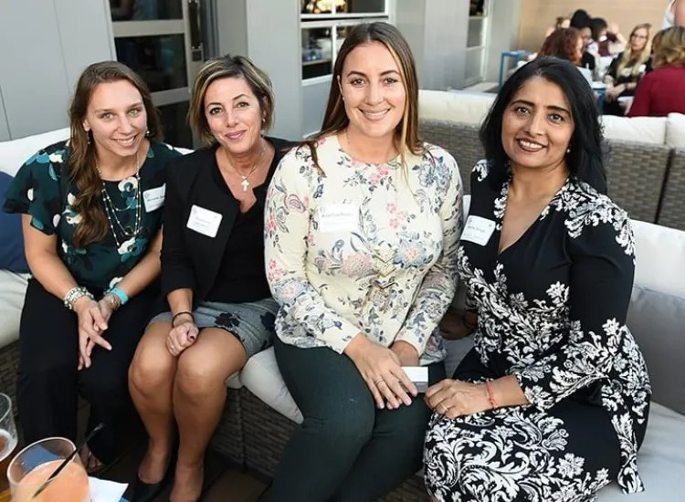 Four women sit on a couch during a networking event.