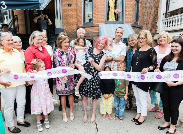 A group of people stand outside Palette Cafe at a ceremonial ribbon  cutting.