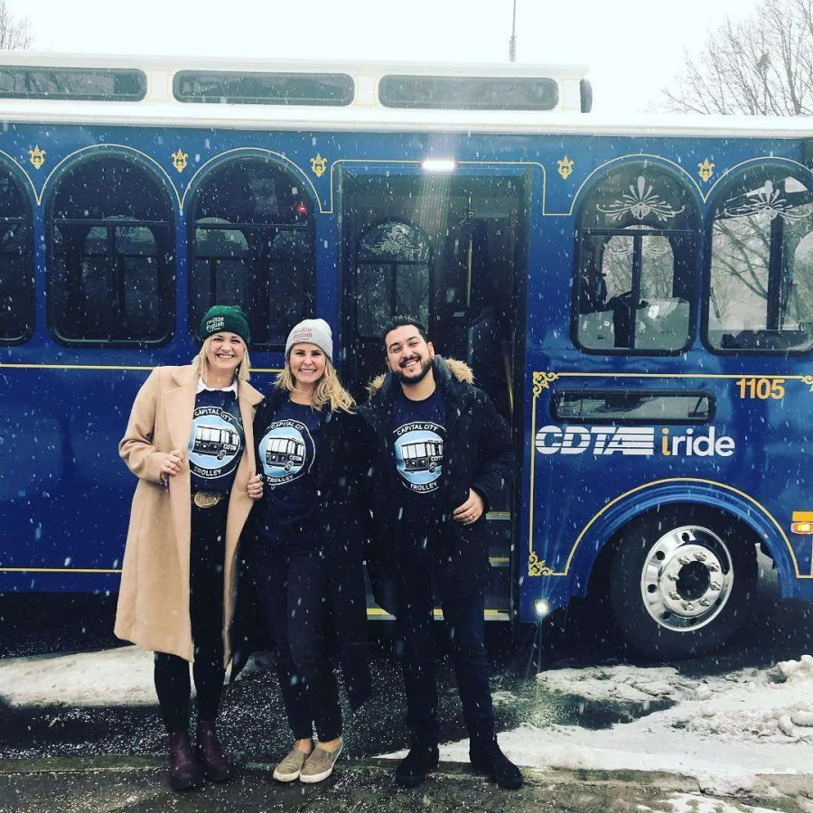 Three people stand outside a CDTA trolley to promote their sustainability programs