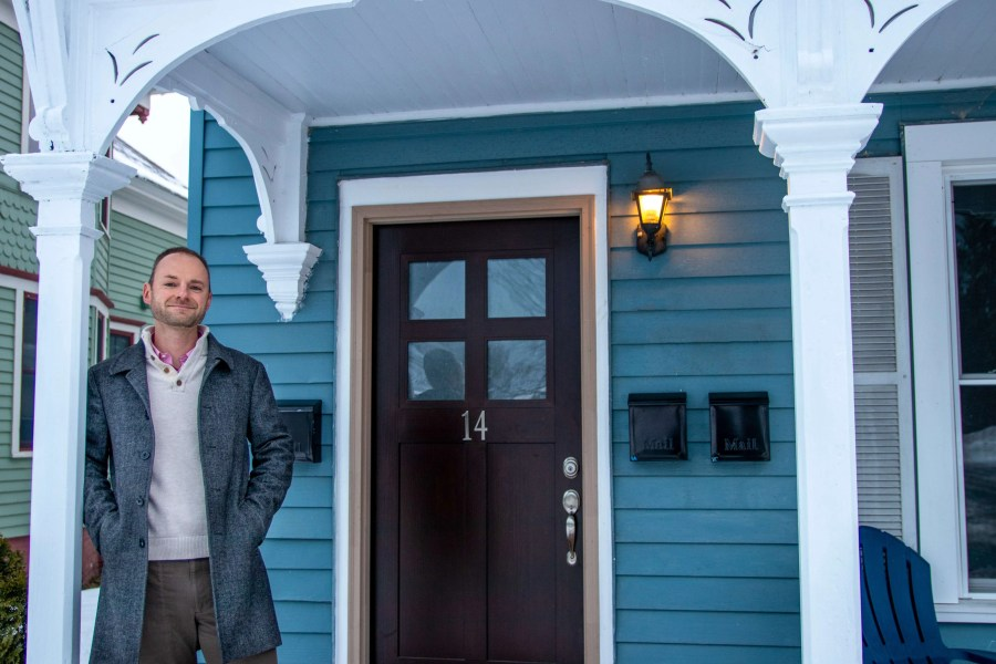 Gentleman in business casual attire stands and smiles on the front porch of his new home.