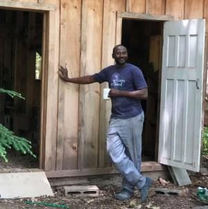 Ben Traore in front of a chicken coop