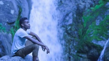 Kulton The Maker sitting by a waterfall