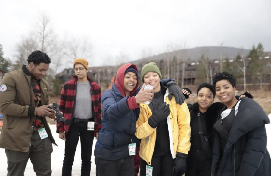 A group of young adults stand outside at a ski resort while on person takes a selfie  Photo by: konradodhiambo