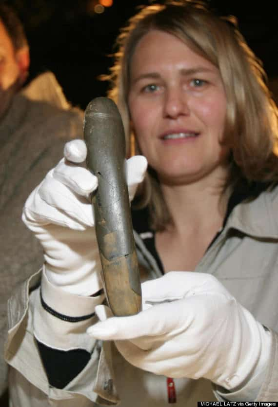 SCHELKLINGEN, Germany: Archaeologist Petra Kieselbach of Germany holds a 28,000 years old stone phallus which has been discovered in a cave in Baden-Wuertemberg in southern Germany, during a press conference in Schelklingen 25 July 2005. In assembling 14 stone fragments, found last year in the Hohle Fels cave, archeologists rebuilt the phallus, which is 20 centimeters (eight inches) long and three centimeters wide. AFP PHOTO DDP/MICHAEL LATZ GERMANY OUT (Photo credit MICHAEL LATZ/AFP/Getty Images)