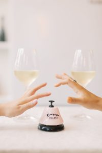 two wine glasses with women hands competing to press the buzzer first.